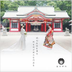 春日神社本殿をバックに立つ、色打掛とドレスをまとった花嫁